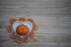 Изображение фотографии еды здорового апельсина с вычерченным на счастливой улыбке и в блюде формы сердца влюбленности с космосом  стоковое фото