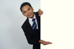 Изображение фото молодого азиатского бизнесмена держа пустой знак с показывать жест Стоковая Фотография RF