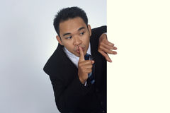 Изображение фото молодого азиатского бизнесмена держа пустой знак с молчаливым жестом Стоковое Изображение