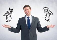 Изображение цифров составное бизнесмена держа ангела и демона Стоковое фото RF