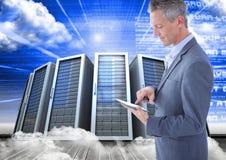 Изображение цифров составное бизнесмена используя цифровую таблетку против башни сервера Стоковая Фотография
