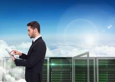 Изображение цифров составное бизнесмена используя цифровую таблетку против башни сервера стоковые фотографии rf