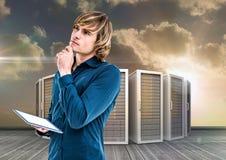 Изображение цифров составное бизнесмена используя цифровую таблетку против башни сервера Стоковые Изображения