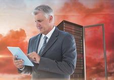 Изображение цифров составное бизнесмена используя цифровую таблетку против башни сервера Стоковая Фотография RF