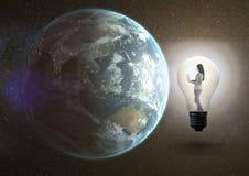 Изображение цифров составное девушки используя компьтер-книжку в электрической лампочке Стоковое фото RF