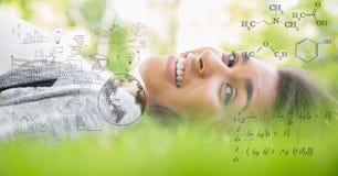 Изображение цифров составное счастливой женщины лежа на траве с уровнениями Стоковое Изображение RF