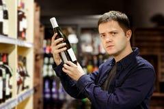 Изображение человека брюнета с бутылкой вина около полок с бутылками стоковая фотография