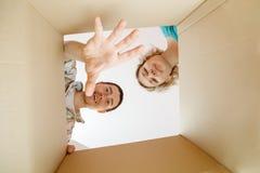 Изображение человека и женщины всматриваясь в картонную коробку Стоковое Фото