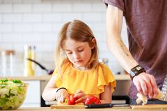 Изображение человека при дочь варя овощи стоковая фотография