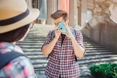 Изображение человека стоя и фотографируя молодая женщина через камеру Он сконцентрирован Женский туристский взгляд на стоковые фото