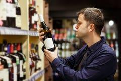 Изображение человека с бутылкой вина около полок с бутылками стоковые фото