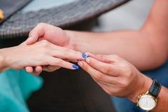 Изображение человека кладя кольцо захвата серебряное на руку женщины, внешнее Стоковые Изображения