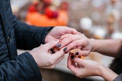 Изображение человека кладя кольцо захвата серебряное на руку женщины, внешнее осенняя пуща Стоковое Изображение