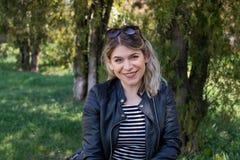 Женщина сидя в парке стоковое изображение