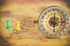 Изображение штырей прикрепленных к карте, показывающ назначение положения или перемещения рядом с винтажным компасом Селективный  стоковое изображение