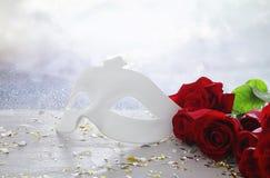 Изображение элегантных венецианских маски и красных роз над деревянным столом Стоковые Фото