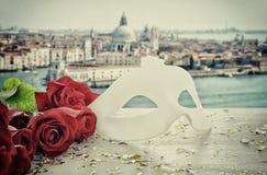 Изображение элегантных венецианских маски и красных роз над деревянным столом перед расплывчатой предпосылкой Венеции Стоковое фото RF
