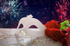 Изображение элегантных венецианских маски и красных роз над деревянным столом Стоковые Изображения RF