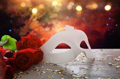 Изображение элегантных венецианских маски и красных роз над деревянным столом Стоковые Фотографии RF