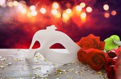 Изображение элегантных венецианских маски и красных роз над деревянным столом Стоковое Изображение