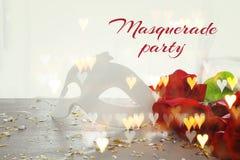 Изображение элегантных венецианских маски и красных роз на деревянном столе Стоковые Фото