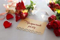 Изображение элегантных венецианских маски и красных роз на деревянном столе Стоковая Фотография