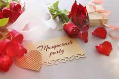 Изображение элегантных венецианских маски и красных роз на деревянном столе Стоковое Изображение