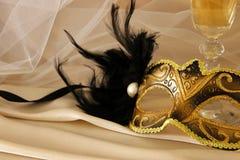 Изображение элегантных венецианских маски и стекла шампанского над золотом Стоковое Изображение