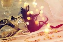 Изображение элегантных венецианских маски и стекла шампанского над золотом Стоковая Фотография RF