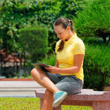 Изображение элегантной маленькой девочки используя ПК таблетки, сидя на быть Стоковая Фотография RF