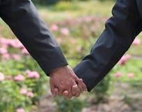 Изображение 2 людей держа руки на свадьбе гомосексуалиста Стоковые Фото