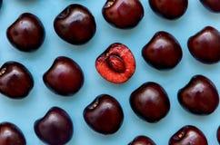 Изображение яркой бургундской вишни на голубой предпосылке Стоковая Фотография RF