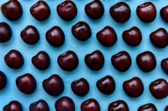 Изображение яркой бургундской вишни на голубой предпосылке Стоковое Фото