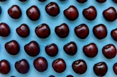 Изображение яркой бургундской вишни на голубой предпосылке Стоковые Изображения