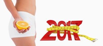 изображение 3DComposite худенького женского тела держа половинный апельсин стоковые фотографии rf