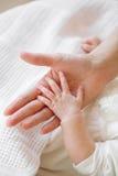 Изображение newborn руки младенца над женской ладонью Стоковые Изображения RF