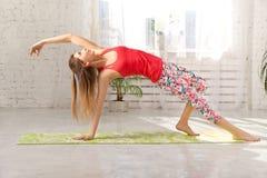 Изображение sporty красивой белокурой молодой женщины в sportswear разрабатывая в зале, делая изменение представления моста стоковое изображение rf