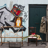 2 изображения висят с изображением Иисуса Христоса на голубой загородке Под загородкой стул Букет гладиолуса кладет на стул Стоковая Фотография