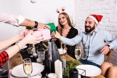 Изобразите показывать группу в составе друзья празднуя рождество дома и давая настоящие моменты друг к другу Стоковое Фото
