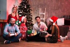 Изобразите показывать группу в составе друзья с подарками на рождество на партии дома Стоковая Фотография