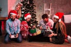 Изобразите показывать группу в составе друзья с подарками на рождество на партии дома Стоковые Фотографии RF