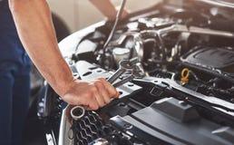 Изобразите показывать мышечного работника обслуживания автомобиля ремонтируя корабль стоковые фотографии rf