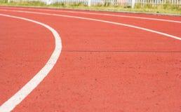 Изогните красный третбан на стадионе и белую линию на предпосылке нерезкости стоковые изображения rf