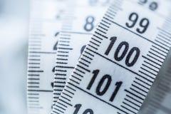 Изогнутая измеряя лента изолированная предпосылкой измеряя белизна ленты портноя Крупный план соперничает Стоковые Фото