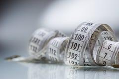 Изогнутая измеряя лента изолированная предпосылкой измеряя белизна ленты портноя Крупный план соперничает Стоковое Фото