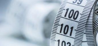Изогнутая измеряя лента изолированная предпосылкой измеряя белизна ленты портноя Крупный план соперничает Стоковая Фотография