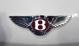 Изогнуто логотип на белом теле автомобиля Bentley едет на автомобиле ограниченный великобританский изготовитель  стоковые фото