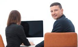 изолированная белизна вид сзади бизнесмен сидя на столе и смотря камеру Стоковое Фото