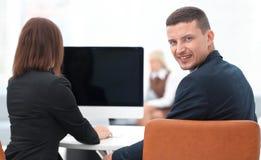 изолированная белизна вид сзади бизнесмен сидя на столе и смотря камеру Стоковые Изображения