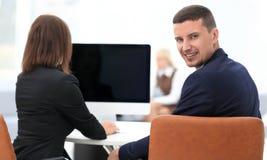 изолированная белизна вид сзади бизнесмен сидя на столе и смотря камеру Стоковое Изображение RF